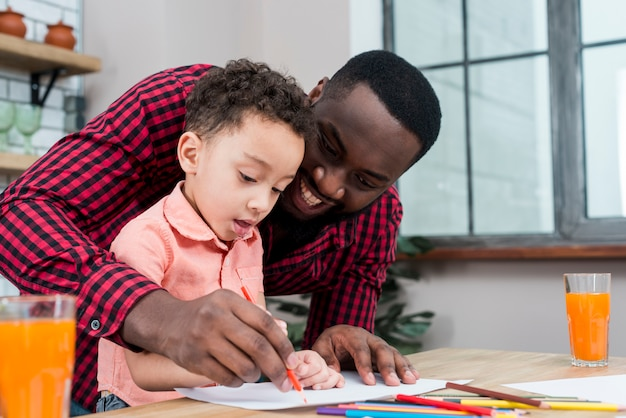 Happy black father and son drawing at table