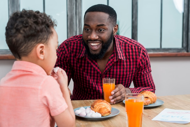 Happy black father and son having breakfast