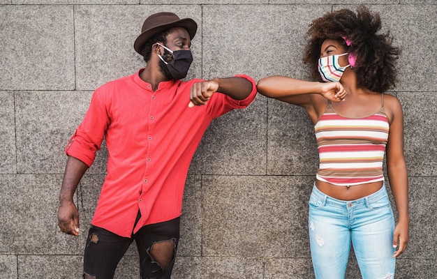 抱擁で挨拶する代わりに肘をぶつけながら保護マスクを身に着けている幸せな黒人の友人-顔に焦点を当てる
