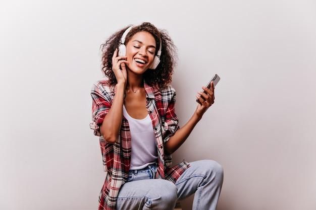 이어폰에 빨간 셔츠 듣는 음악에 행복 한 흑인 여자. 좋아하는 노래와 함께 오싹한 곱슬 헤어 스타일으로 화려한 젊은 여자.
