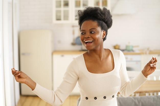 행복 한 흑인 여자는 집에서 혼자 재미, 음악을 듣고 즐기는 춤 패션 드레스를 착용.