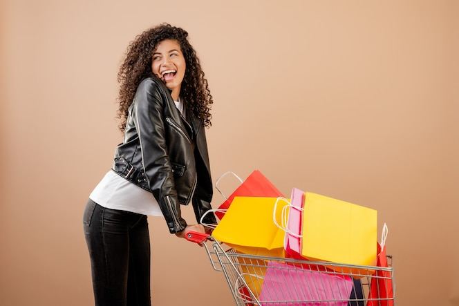Happy black girl with shopping cart full of colorful bags isolated over brown