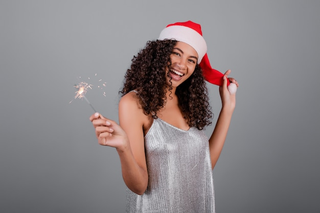 Happy black girl with sparkling sparklers wearing christmas hat and dress isolated over grey