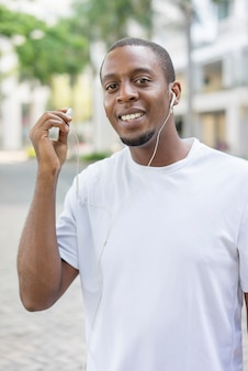 Happy black guy in white tshirt walking outdoors with earphones and enjoying music.