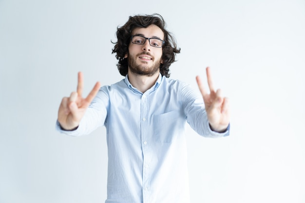 Happy black-haired man showing two victory signs