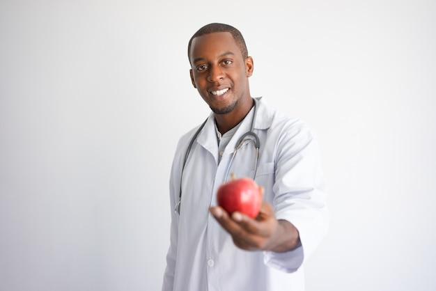 Счастливый черный мужчина-врач держит и предлагает красное яблоко.