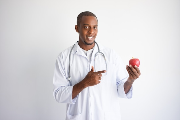 Happy black male doctor holding and pointing at apple.