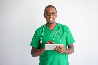 Happy black male doctor using tablet computer. Technology in medicine concept.
