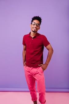 自信を持ってポーズで立っている幸せな黒人男性モデル。ピンクのズボンと赤いtシャツでのんびりと笑顔の男。