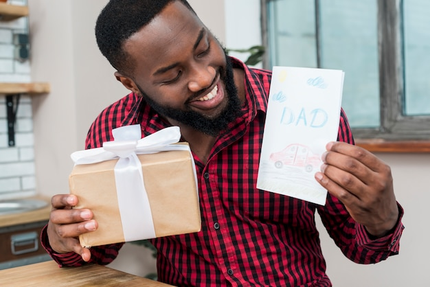 Happy black man holding greeting card and gift