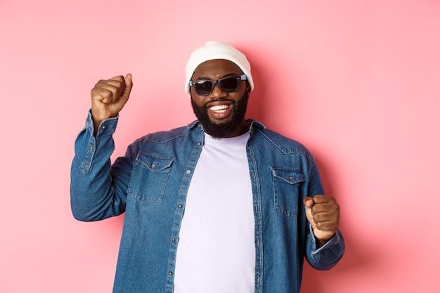 Счастливый черный человек в шапочке и солнцезащитных очках радуется, танцует со счастливым лицом, стоя на розовом фоне