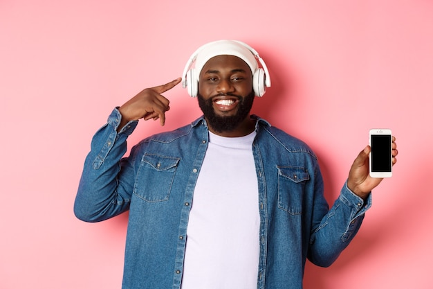 Happy black man listening music, pointing finger at headphones and smiling, showing mobile phone screen app or playlist, standing over pink background