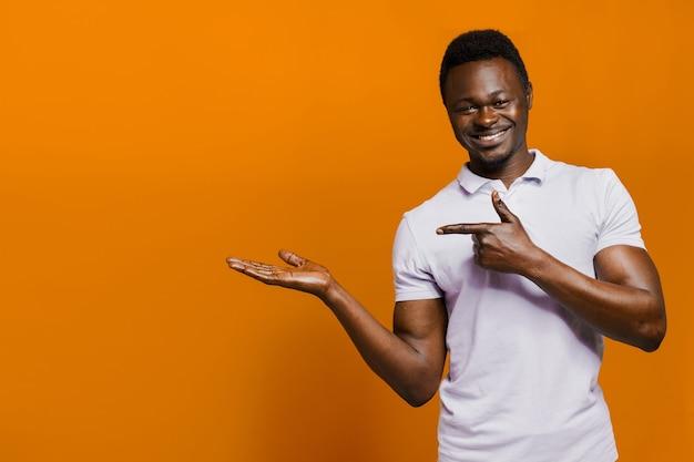 행복한 흑인 남자는 하얀 치아로 웃고 광고를 위한 빈 공간이 있는 왼쪽을 가리킵니다. 아프리카 고립 된 오렌지 배경입니다.