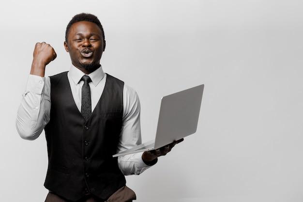 Счастливый темнокожий мужчина выигрывает деньги в онлайн-лотерее