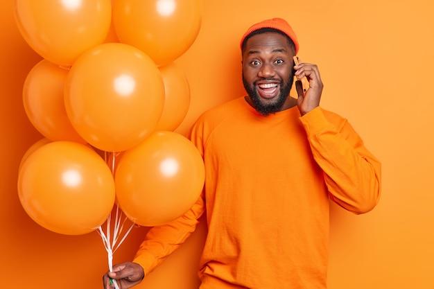 Счастливый темнокожий мужчина с густой бородой празднует день рождения, разговаривает с гелиевыми шарами по мобильному телефону, одетый небрежно, с веселым выражением лица изолирован на оранжевой стене