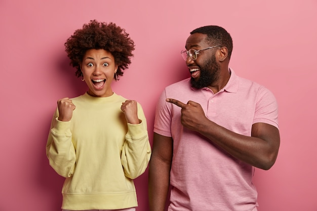 Happy black man with thick beard points at triumphing woman with clenched fists, celebrates success, exclaims joyfully, expresses positive emotions. look