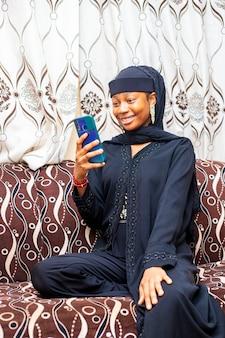 스마트 폰 앱을 들고 있는 행복한 흑인 이슬람 10대 소녀가 원격 모바일 채팅 가상 회의, 집에서 소셜 미디어에서 친구들과 온라인 가상 채팅 화상 통화를 즐기고 있습니다.