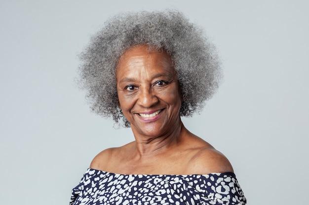スタジオ撮影で幸せな黒人の年配の女性