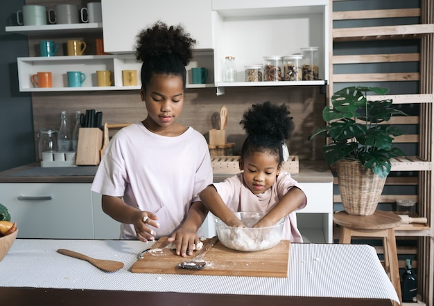 Happy black sisters threshing flour in the kitchen