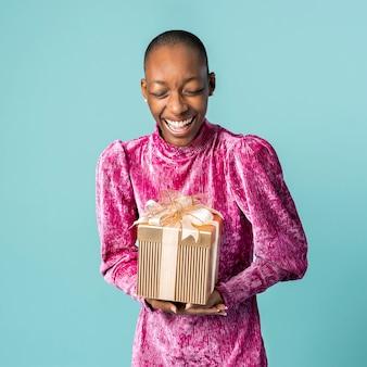 Счастливая черная женщина, держащая подарочную коробку