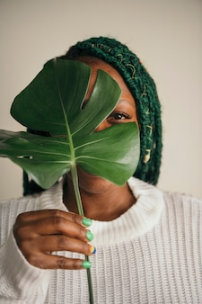 Happy black woman holding a leaf over her face