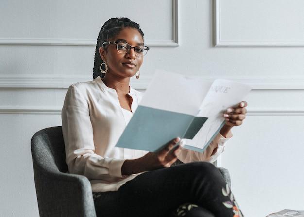 Счастливая черная женщина, читающая уникальный журнал