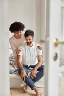 Счастливая темнокожая женщина показывает мужу тест на беременность, довольная положительным результатом, позирует в спальне современной квартиры, радуется хорошим новостям, готова стать родителями. семейная пара в помещении. отцовство