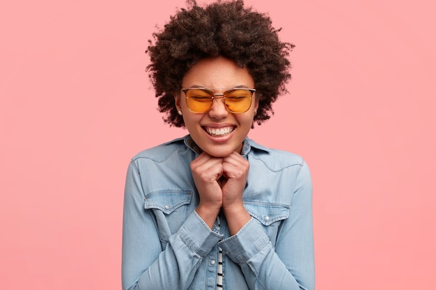 Happy black woman squints face from pleasure, smiles broadly, shows white teeth, keeps both hands under chin, wears yellow sunglasses, rejoices marriage proposal, isolated over pink wall