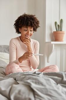 Felice donna nera con acconciatura afro, guarda positivamente al test di gravidanza