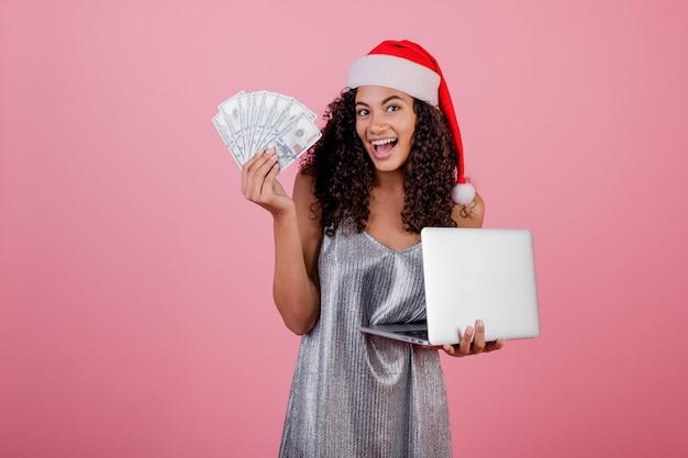 Счастливая чернокожая женщина с долларами и компьтер-книжкой нося праздника нося шляпу и платье santa изолированные над пинком