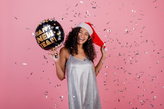 Happy black woman with happy new year balloon and confetti flying in the air isolated over pink