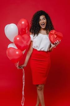 심장 모양의 선물 상자와 화려한 풍선 빨간 벽에 고립 된 행복 한 흑인 여자