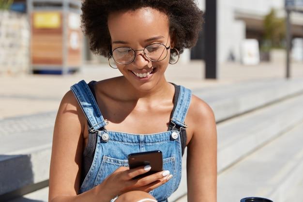 기뻐하는 표정을 지닌 행복한 흑인 여성, 거리 산책, 탐색 경로 확인, 온라인 지불을 위해 현대 휴대 전화 사용, 둥근 안경 착용, 흐린 야외 포즈