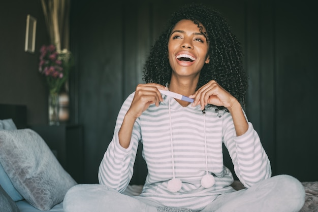 Happy black woman with a pregnancy test on bed