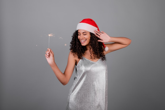 Happy black woman with sparkling sparklers wearing christmas hat and dress isolated over grey
