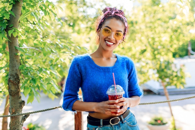 Happy black woman with stylish  hairstyle with headband spending her weekend in the park, walking and drinking lemonade.