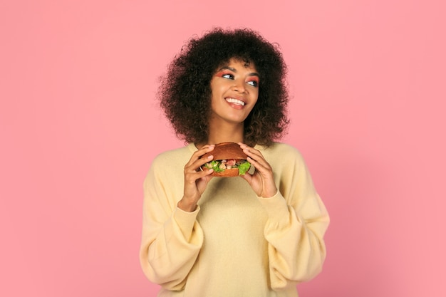 Счастливая черная женщина с волнистыми волосами ест вкусный чизбургер на розовом.