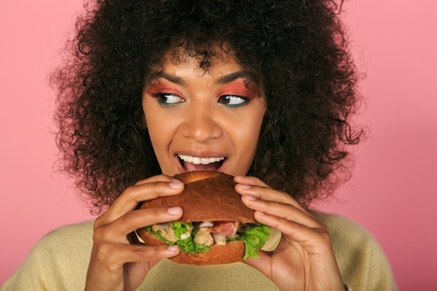 Happy black woman with wavy hairs eating tasty cheeseburger on pink.
