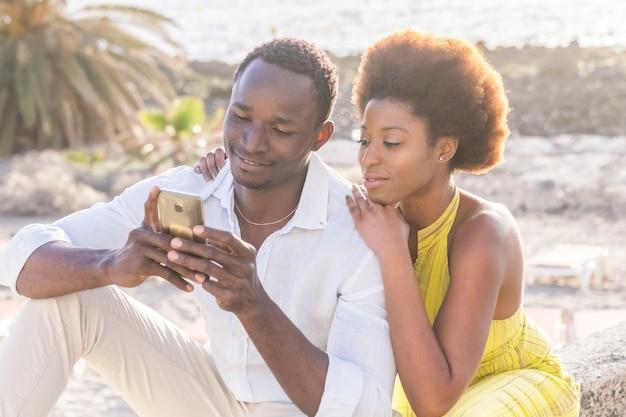 夕日の逆光を背景に、ビーチで幸せな黒人の若いカップル、スマートフォンを使って友達とチャットしたり、休暇中の写真を見たり、笑顔で笑う