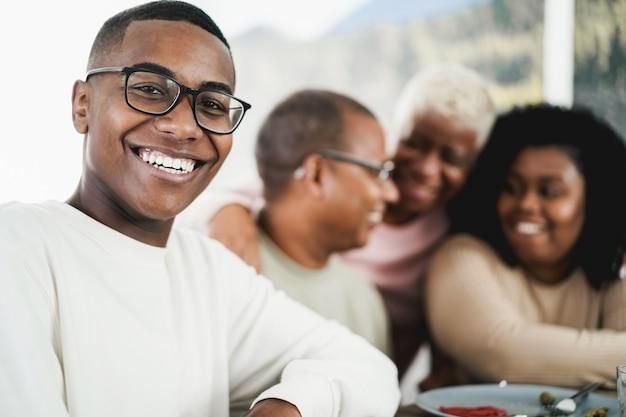 집에서 그의 가족과 함께 점심을 먹고 행복 흑인 젊은 남자