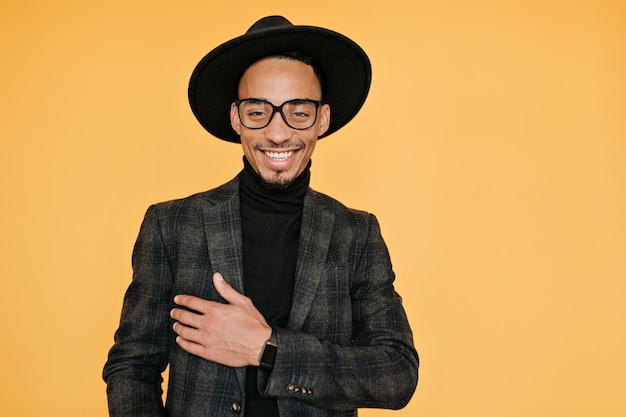 Happy black young man wears elegant dark suit posing with pleased smile. indoor photo of relaxed mulatto male model in glasses enjoying photoshoot.