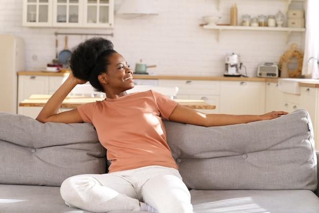 행복 한 흑인 젊은 여자는 집에서 아늑한 소파에 쉬고, 멀리보고 게으른 주말을 즐길 수 있습니다. 스트레스 무료