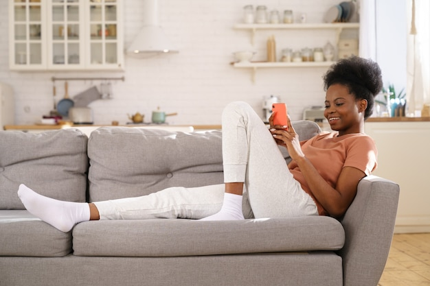 Happy black young woman resting on cozy sofa at home, using smartphone, chatting in social networks.