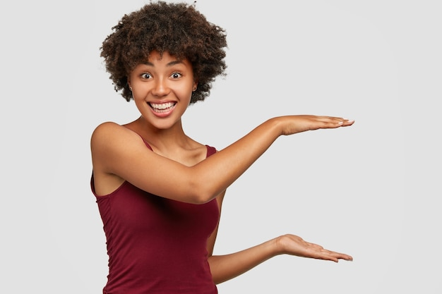 Happy black young woman with pleased facial expression shows height of something