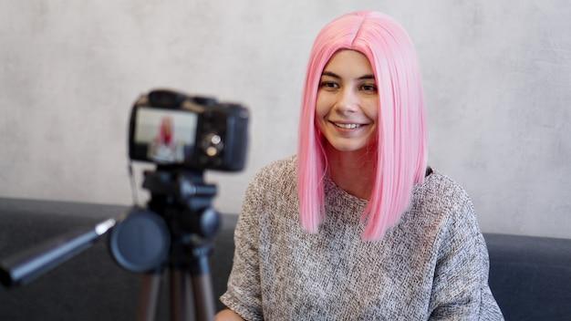 三脚のカメラの前にピンクのかつらで幸せなブロガー。彼女はビデオを録画します