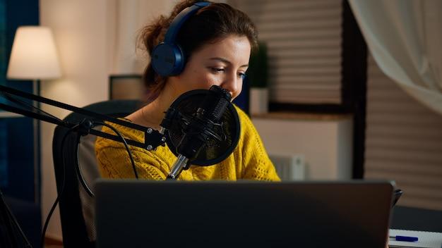 Blogger felice che legge i messaggi dei fan utilizzando lo smartphone seduto nello studio podcast di casa durante il livestreaming, la registrazione. spettacolo online produzione in onda host di trasmissione internet in streaming di contenuti live