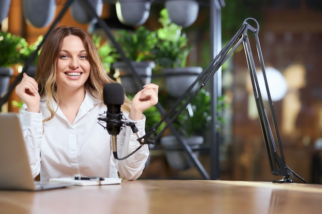 Happy blogger woman giving interview into microphone