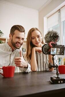 Счастливые блогеры пара позитивных блоггеров записывают новое видео для своего блога бородатый мужчина показывает