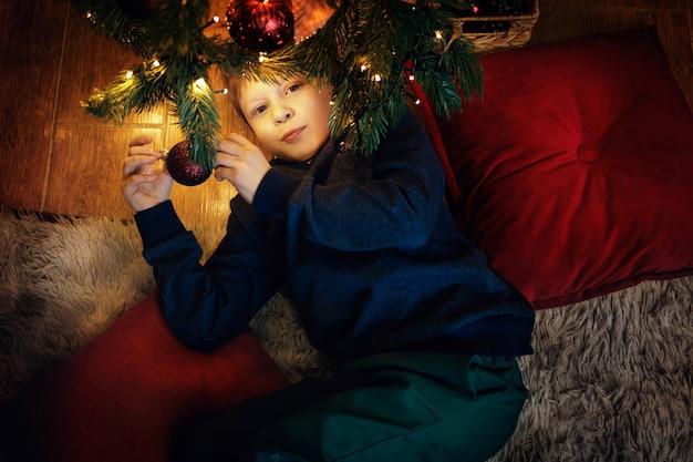 57歳の幸せな金髪の少年は、カメラを見ている新年の木の近くのカーペットの上に横たわっています