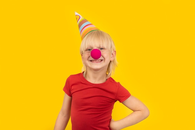 Happy blond boy in party hat and with red clown nose smiles for the camera. celebrating birthday.